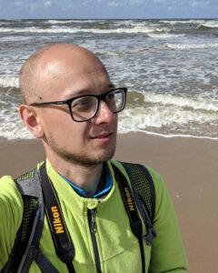 Hendryk in gelbergrüner Fleecejacke am Strand, das anlaufende Meer im Hintergrund. Man sieht die Träger seines Rucksacks und den Nikon-Kameragurt um den Hals.