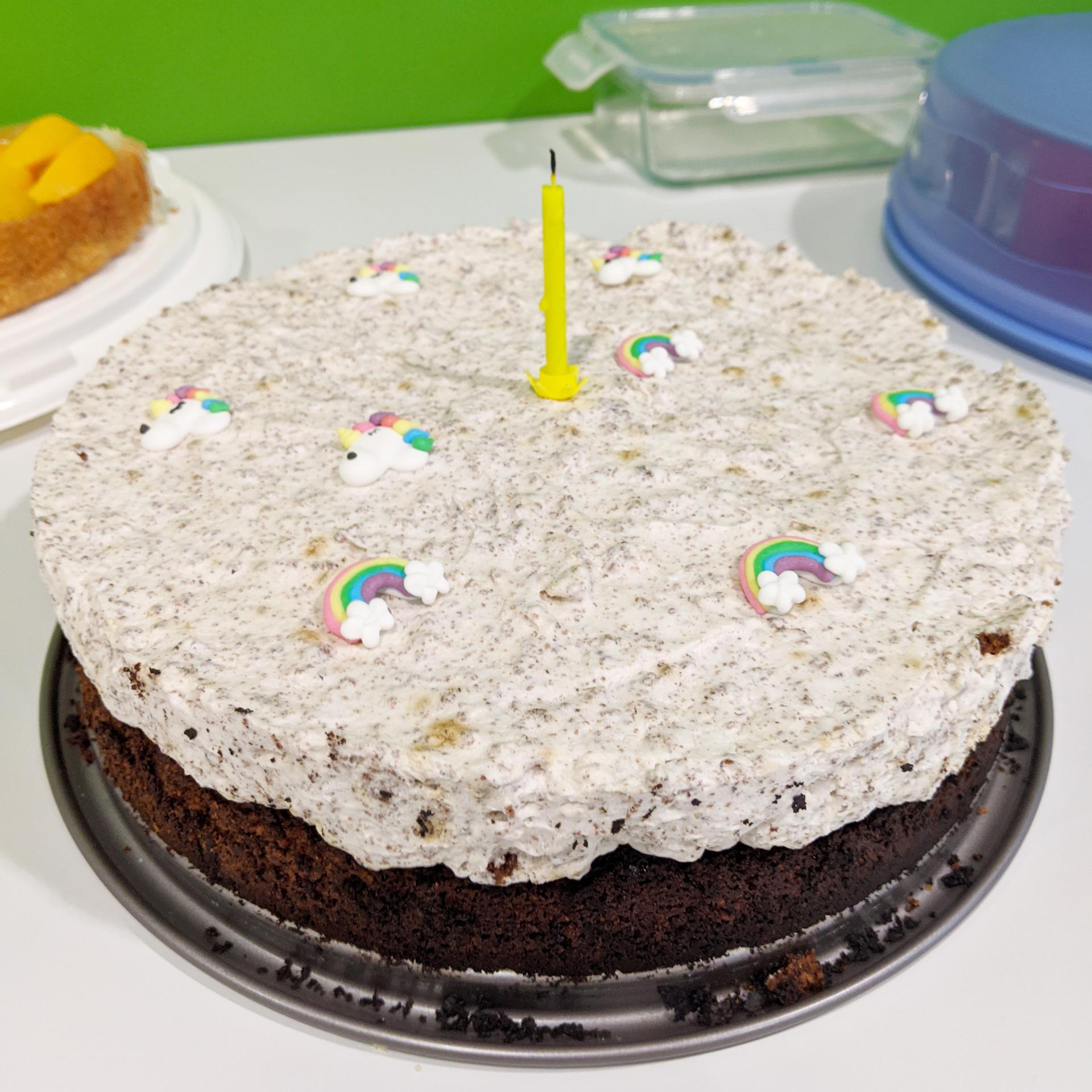 Krümel-Sahne-Torte dekoriert mit Einhörnern und einer gelben Geburtstagkerze